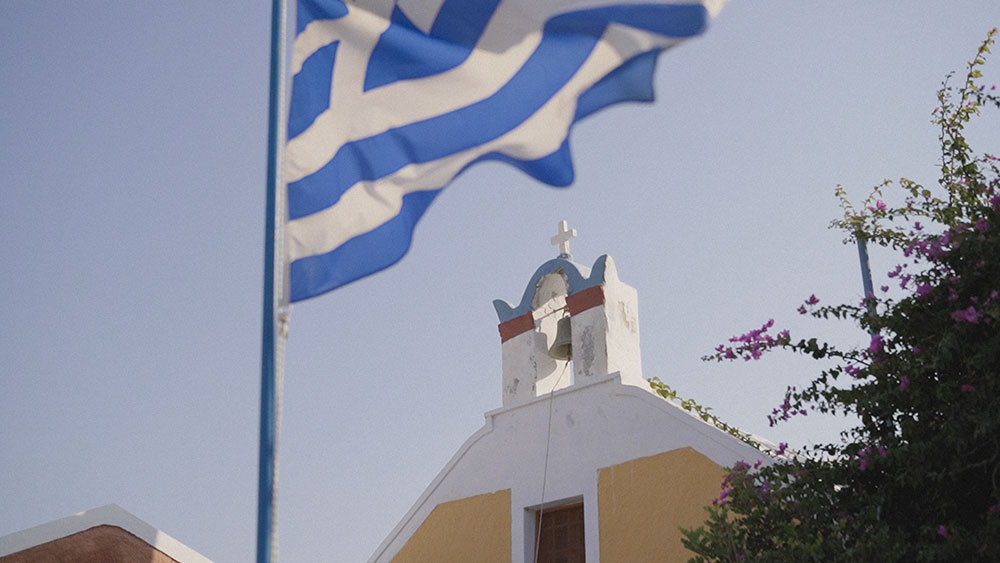 greece flag church santorini oia wedding videographer